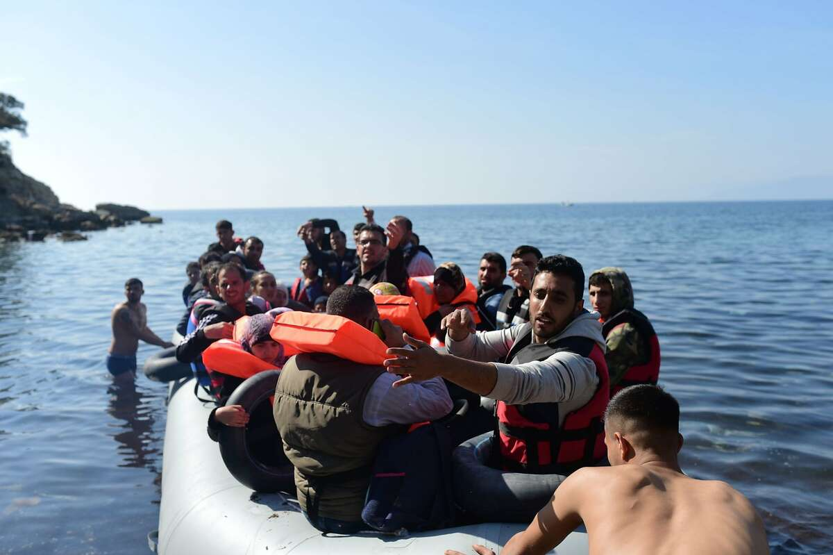Syrian migrants sit in a dinghy as they attempt to cross the Aegean Sea to the Greek island of Lesbos from the Ayvacik coast in Canakkale on February 28, 2016. The number of asylum-seekers entering Greece from Turkey continues unabated and the border closures along the Balkan route