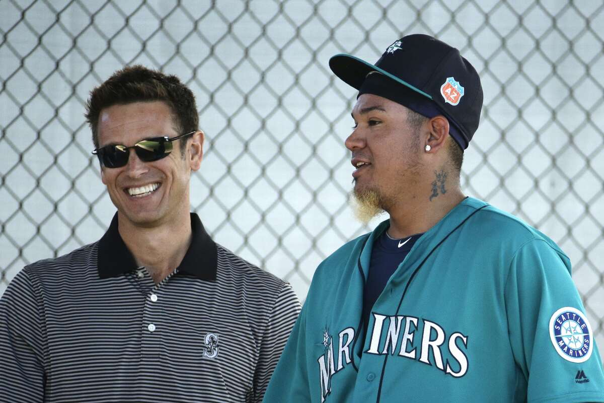 Seattle Mariners starting pitcher Felix Hernandez talks with general manager Jerry Dipoto after throwing during spring training baseball practice Saturday, Feb. 27, 2016, in Peoria, Ariz. (AP Photo/Charlie Riedel)