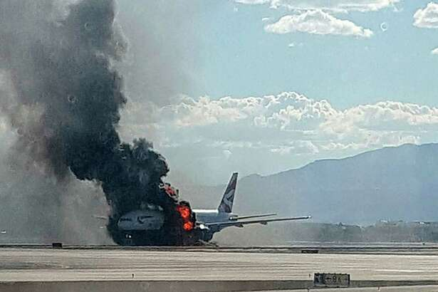 FILE - In this Sept. 8, 2015, file photo, taken from the view of a plane window, smoke billows out from a plane that caught fire at McCarren International Airport in Las Vegas. Officials say flight-worthiness tests are being conducted in Las Vegas on a repaired British Airways jet that caught fire while passengers escaped an aborted takeoff in September. The damaged engine was removed and replaced, and officials said they planned to restore the rest of the big Boeing 777 to airworthiness so it could be flown from McCarran International Airport to repair facilities abroad. (Eric Hays via AP, File) MANDATORY CREDIT