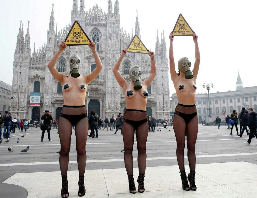 PETA (People for the Ethical Treatment of Animals) activists wear gas masks during a demonstration against the use of fur ahead of Milan's Fashion Week, in Milan's Duomo Square, Italy, Tuesday, Feb. 23, 2016. Milan Fashion Week opens Wednesday. Writing on placards reads in Italian
