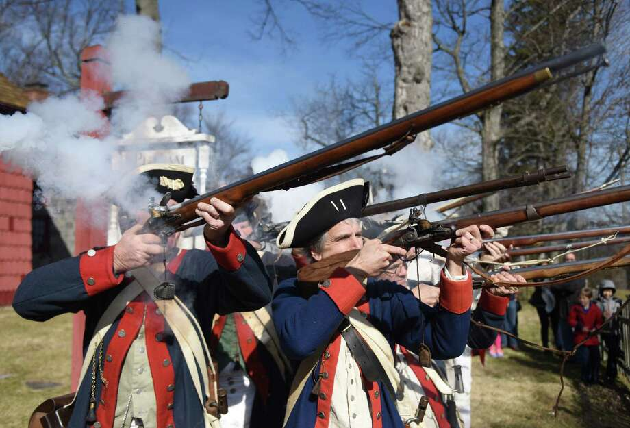 Re-enactors Bob Stiles, left, and Dan Kinley perform a gun demonstration with other members of the Fifth Connecticut Regiment at the Revolutionary War re-enactment of General Israel Putnam's historic ride at Putnam Cottage in Greenwich, Conn. Sunday, Feb. 28, 2016. The event, hosted by the Daughters of the American Revolution, featured gun and cannon demonstrations, a military encampment, tactical exercises, colonial life demonstrations and cottage tours. Proceeds from the event assist in the preservation of Putnam Cottage. Photo: Tyler Sizemore / Hearst Connecticut Media / Greenwich Time