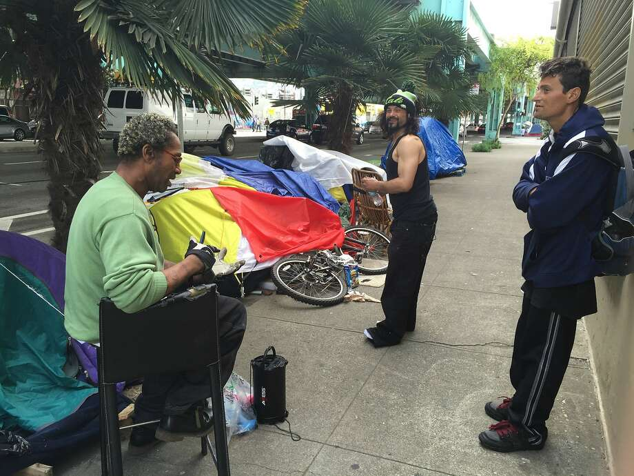 Hoyt Walker, 49, pictured left, and two friends chat near their tents under the Central Freeway in San Francisco. Photo: Evan Sernoffsky
