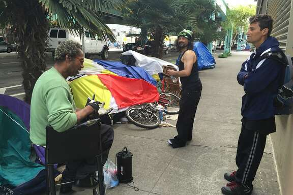 Hoyt Walker, 49, pictured left, and two friends chat near their tents under the Central Freeway in San Francisco.