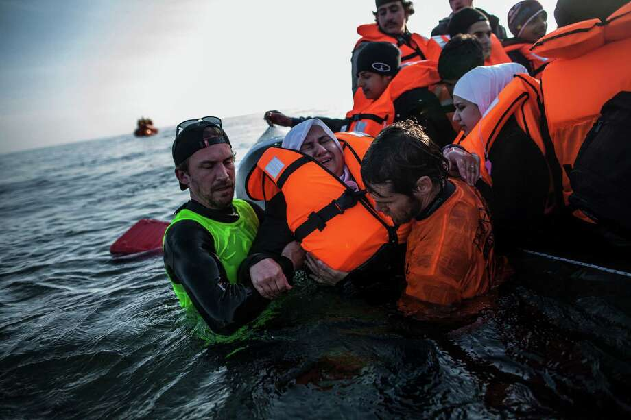 A Syrian refugee is helped by volunteers to leave a sinking dinghy at a beach on the southeastern island of Lesbos, Sunday, Feb. 28, 2016. Greece is mired in a full-blown diplomatic dispute with some EU countries over their border slowdowns and closures. Those border moves have left Greece and the migrants caught between an increasingly fractious Europe, where several countries are reluctant to accept more asylum-seekers, and Turkey, which has appeared unwilling or unable to staunch the torrent of people leaving in barely seaworthy smuggling boats for Greek islands.  (AP Photo/Manu Brabo) Photo: Manu Brabo, STR / AP