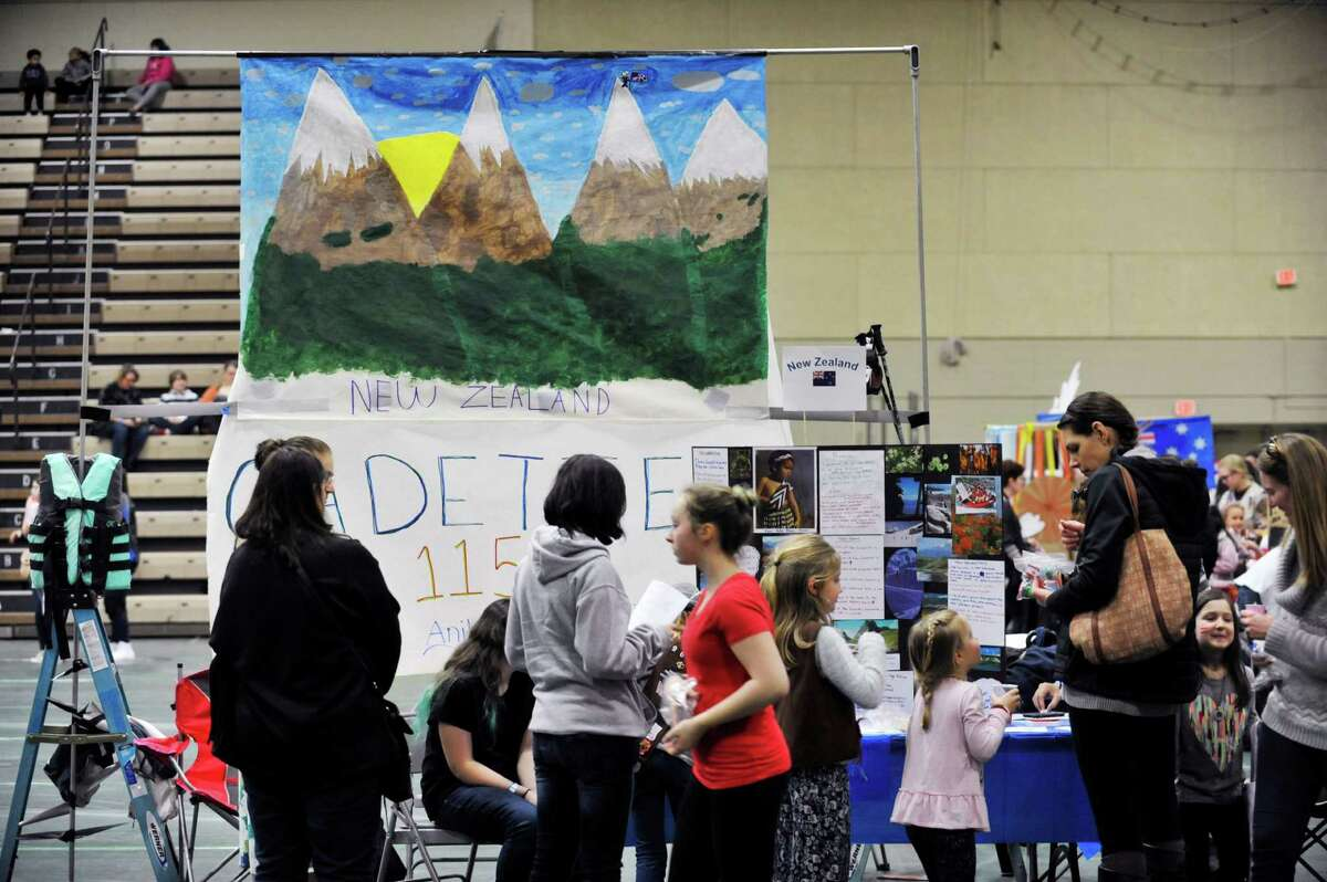 Visitors look over the display on New Zealand by Girl Scout Troop 1159 out of East Greenbush at the 2016 Girl Scout Southern Region International Fair at Hudson Valley Community College on Sunday, Feb. 28, 2016, in Troy, N.Y. This is the 36th year of the international fair, where area Girl Scout troops display the food and culture of different countries. Girl Scouts is an international organization, and every fall Girl Scout troops begin the process of choosing a country and researching it's culture, customs and crafts. The fair is the culmination of the project with the girls presenting the food and other aspects of the country's culture at a display booth. Kelly Morris, chair person of the international fair committee, said that each year roughly 1,000 visitors come through the doors to see the displays and taste the food. Forty-six countries were represented at the fair, with 31 troops taking part Morris said. (Paul Buckowski / Times Union)