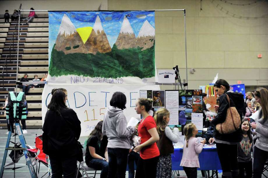 Visitors look over the display on New Zealand by Girl Scout Troop 1159 out of East Greenbush at the 2016 Girl Scout Southern Region International Fair at Hudson Valley Community College on Sunday, Feb. 28, 2016, in Troy, N.Y.  This is the 36th year of the international fair, where area Girl Scout troops display the food and culture of different countries.  Girl Scouts is an international organization, and every fall Girl Scout troops begin the process of choosing a country and researching it's culture, customs and crafts.  The fair is the culmination of the project with the girls presenting the food and other aspects of the country's culture at a display booth.  Kelly Morris, chair person of the international fair committee, said that each year roughly 1,000 visitors come through the doors to see the displays and taste the food.  Forty-six countries were represented at the fair, with 31 troops taking part Morris said.   (Paul Buckowski / Times Union) Photo: PAUL BUCKOWSKI / 10035534A