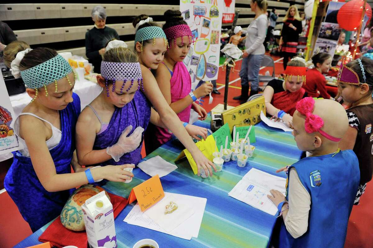 Girl Scout Troop 1265 members out of Averill Park, from left to right, Natalie LeFrancois, Ally Bendett, Grace Bursey, Carynne Jewel and Annika Silver hand out samples of food from the country of Sri Lanka at the 2016 Girl Scout Southern Region International Fair at Hudson Valley Community College on Sunday, Feb. 28, 2016, in Troy, N.Y. This is the 36th year of the international fair, where area Girl Scout troops display the food and culture of different countries. Girl Scouts is an international organization, and every fall Girl Scout troops begin the process of choosing a country and researching it's culture, customs and crafts. The fair is the culmination of the project with the girls presenting the food and other aspects of the country's culture at a display booth. Kelly Morris, chair person of the international fair committee, said that each year roughly 1,000 visitors come through the doors to see the displays and taste the food. Forty-six countries were represented at the fair, with 31 troops taking part Morris said. (Paul Buckowski / Times Union)