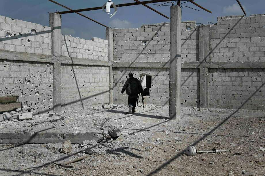 A Syrian rebel fighter from the Failaq al-Rahman brigade patrols inside a building on the frontline against regime forces in the village of Bala, Syria, on Sunday.  Photo: ABDULMONAM EASSA, Stringer / AFP or licensors