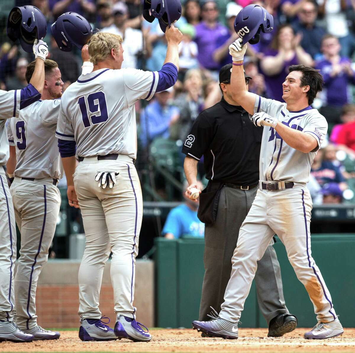 TCU outfielder Josh Watson (7) is greeted at home by TCU first baseman Luken Baker (19) after hitting a three-run home run off Houston starter Mitch Ullom during the third inning of a Houston College Classic baseball game at Minute Maid Park on Sunday, Feb. 28, 2016, in Houston.