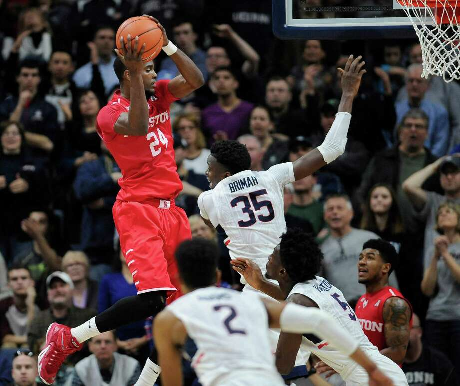 UH's Devonta Pollard, left, separates himself from Connecticut's Amida Brimah and the rest of the crowd for a rebound during the second half of the Cougars' 75-68 road victory Sunday. Photo: Jessica Hill, FRE / FR125654 AP