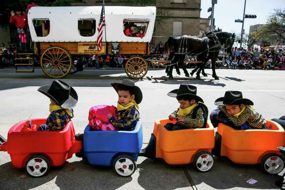 Three-year-old quadruplet brothers, from left, Ace, Blaine, Cash and Dylan Montalvo watch the Rodeo Parade in downtown Houston Saturday, Feb. 27, 2016.