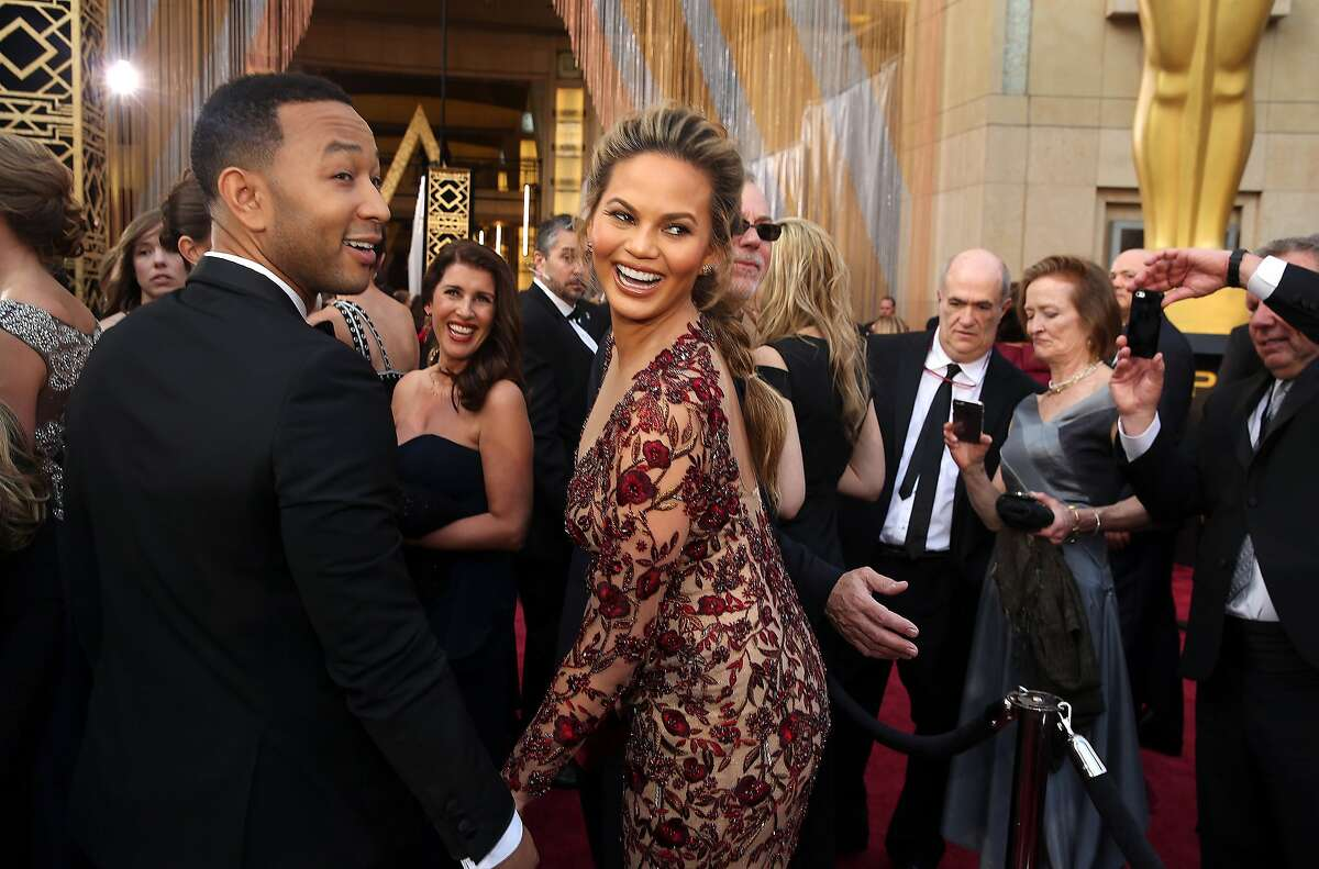 John Legend, left, and Chrissy Teigen arrive at the Oscars on Sunday, Feb. 28, 2016, at the Dolby Theatre in Los Angeles.