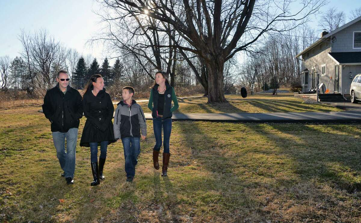 The Bruno family, from left, Rick and Crystal and their children Anthony, 11, and Lexxie, 14 outside their home Friday Feb. 26, 2016 in Latham, NY. A senior housing development is proposed for the land, left, adjacent to their own. Without their knowledge, the town lessened a buffer zone between their property and the neighboring one that enables construction of senior apartments. (John Carl D'Annibale / Times Union)
