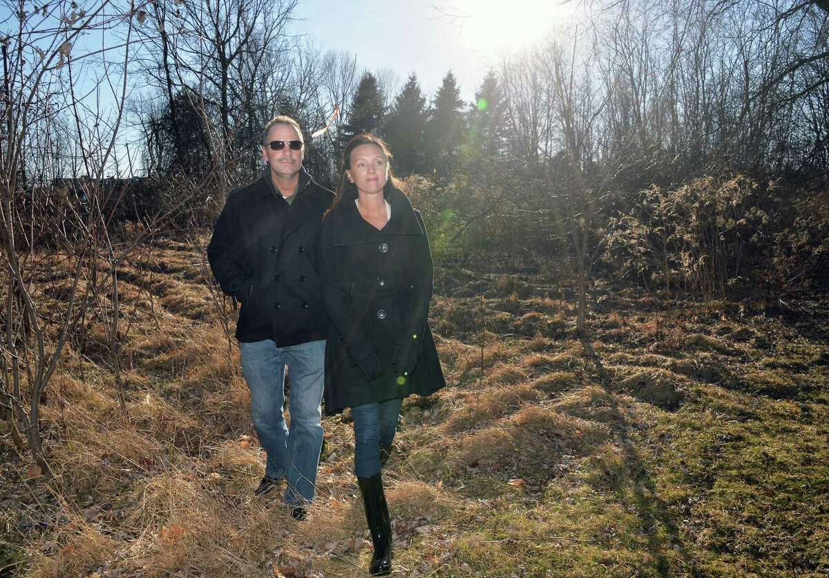 Rick and Crystal Bruno walk along a field outside their home Friday Feb. 26, 2016 in Latham, NY. A senior housing development is proposed for the land adjacent to their own. Without their knowledge, the town lessened a buffer zone between their property and the neighboring one that enables construction of senior apartments. (John Carl D'Annibale / Times Union)