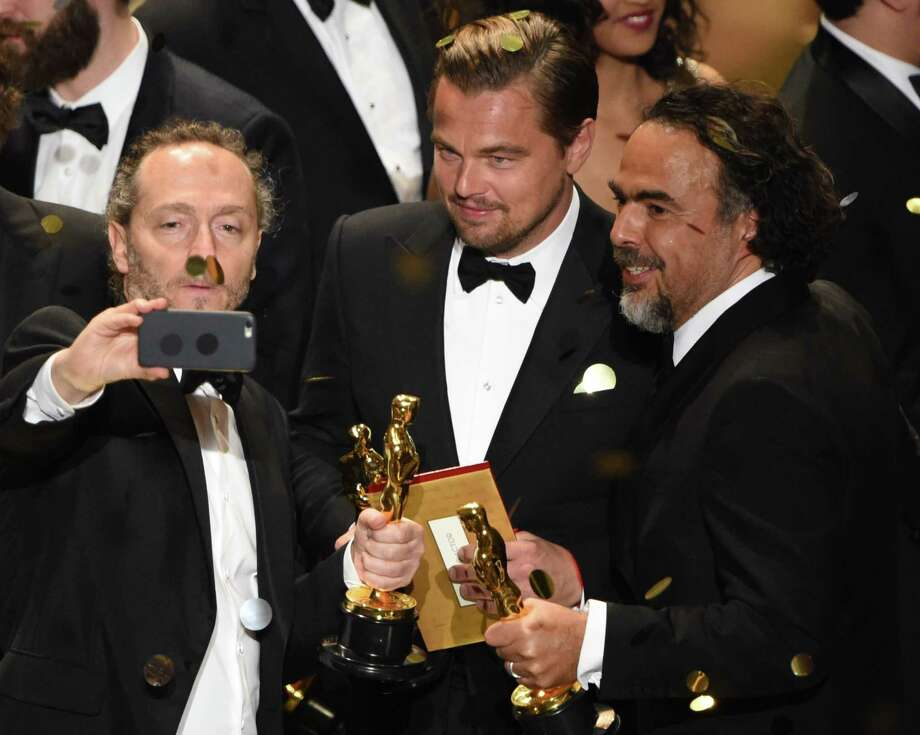 (L to R) Cinematographer Emmanuel Lubezki , Actor Leonardo DiCaprio and Director Alejandro Gonzalez Inarritu pose for a selfie with their awards on stage at the 88th Oscars on February 28, 2016 in Hollywood, California. AFP PHOTO / MARK RALSTONMARK RALSTON/AFP/Getty Images Photo: MARK RALSTON, Staff / AFP