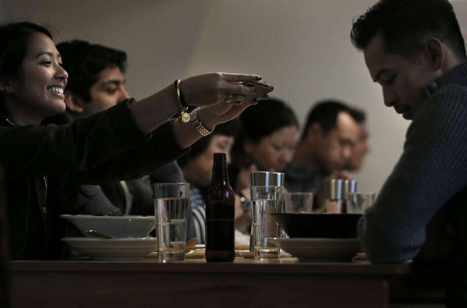 Crissy Lauron (left) photographs her boyfriend Francis Torralba's ramen dinner at Mensho Tokyo in S.F. Photo: Carlos Avila Gonzalez, The Chronicle