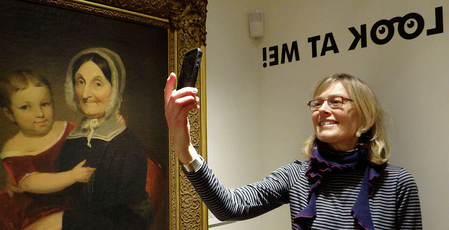 "Sandy Altieri, a board member of the Fairfield Museum and History Center, snaps a selfie at its new ""Look At Me"" exhibit. Photo: Fairfield Citizen / Mike Lauterborn / Fairfield Citizen"
