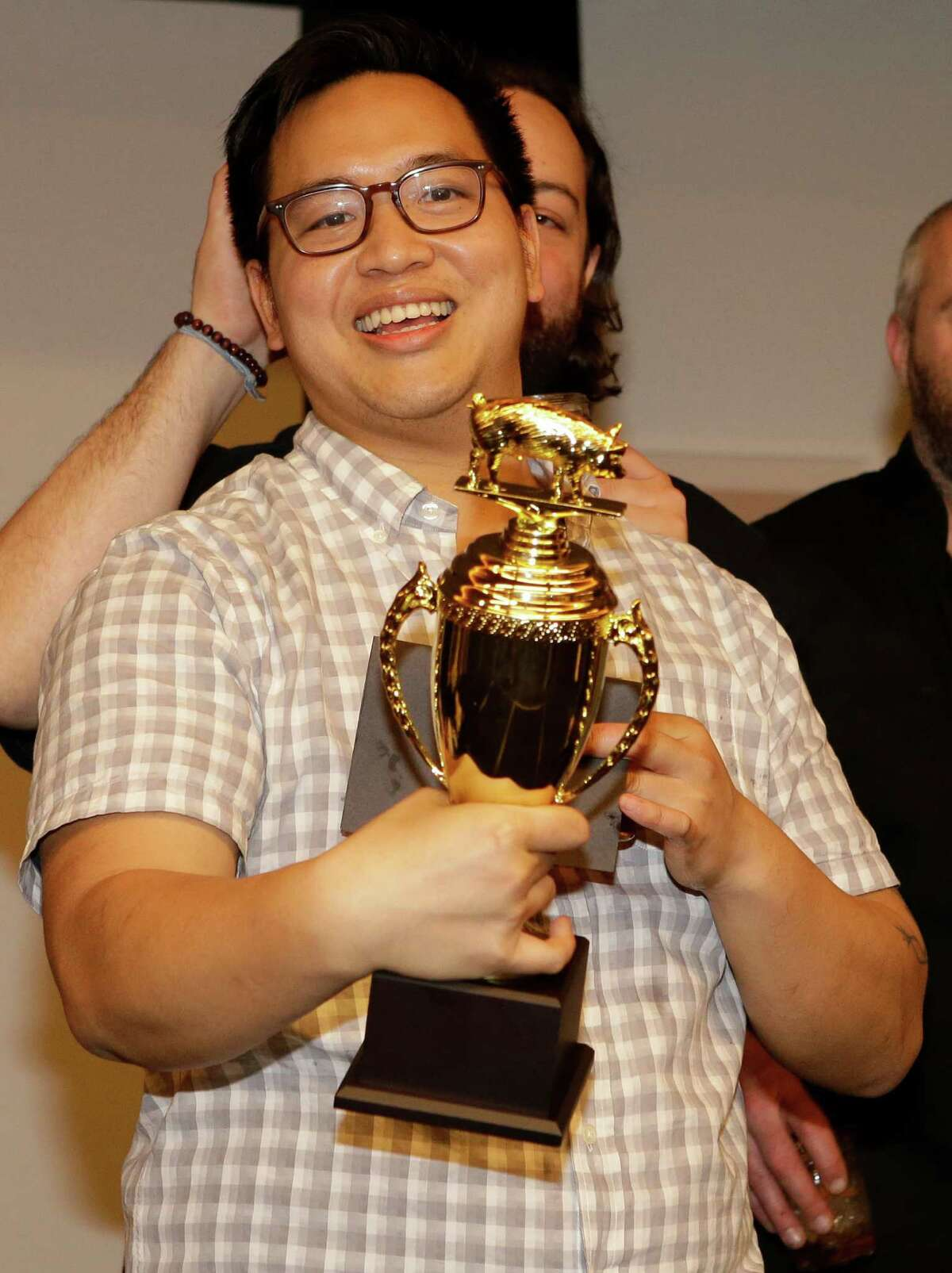 Chef Justin Yu of Oxheart holds his trophy at the Cochon555 event at the JW Marriott Houston Downtown, 806 Main St., Sunday, Feb. 28, 2016, in Houston.