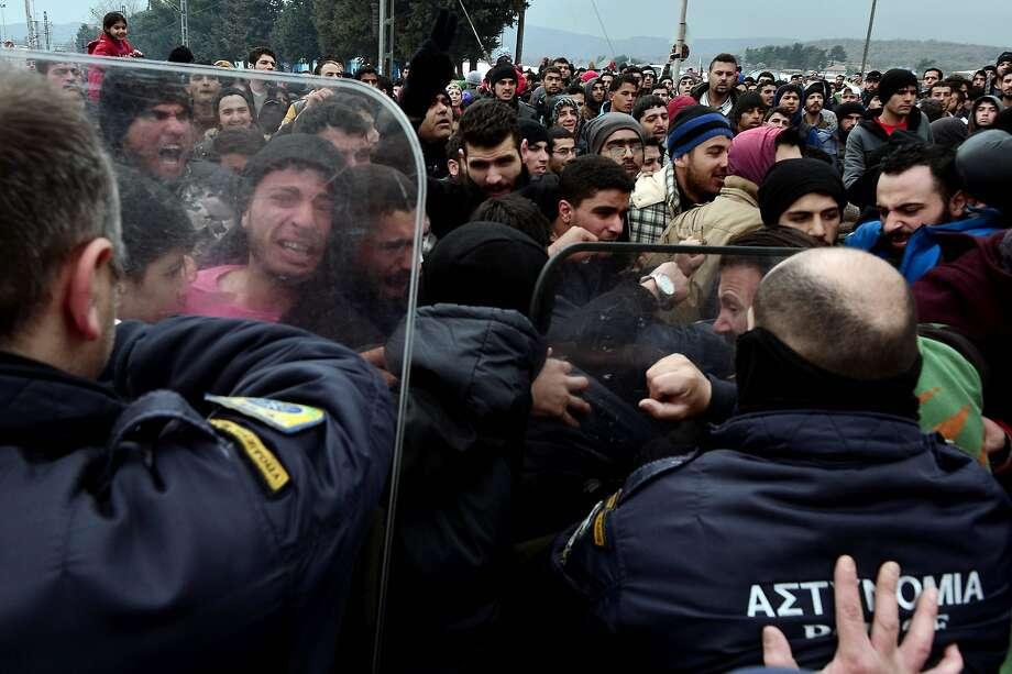 Refugees near the Greek village of Idomeni try to break through a police blockade toward the border fence of Macedonia. Photo: Louisa Gouliamaki, AFP / Getty Images