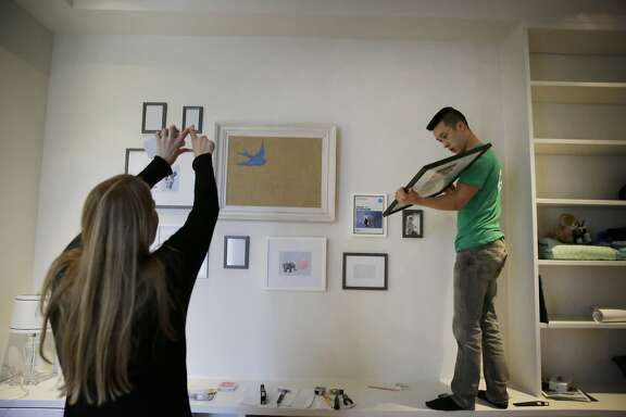 "Thai-can ""Paul"" Nguyen (right), Taskrabbit tasker, checks the back of a frame while consulting with Lauren Fraser (left), San Francisco resident, about the placement of frames as he hangs picture frames in the baby's room for Fraser on Monday, February 29, 2016 in San Francisco, California."