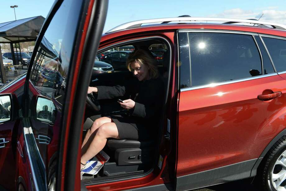 Kathy Lanni tries the seat of a new Ford Escape after being announced as a winner in Price Chopper and Market 32's Bags2Riches contest on Monday, Feb. 29, 2016, at the Market Bistro store in Latham, N.Y. Lanni can choose a new Ford valued at up to $28,500. Shoppers receive one game ticket for every $25 spent using an AdvantEdge card at any of the 136 Price Chopper and Market 32 stores located throughout the Northeast. The contest runs through March 19, 2016; more than $8 million in prizes are available. (Will Waldron/Times Union) Photo: Will Waldron / 10035626A