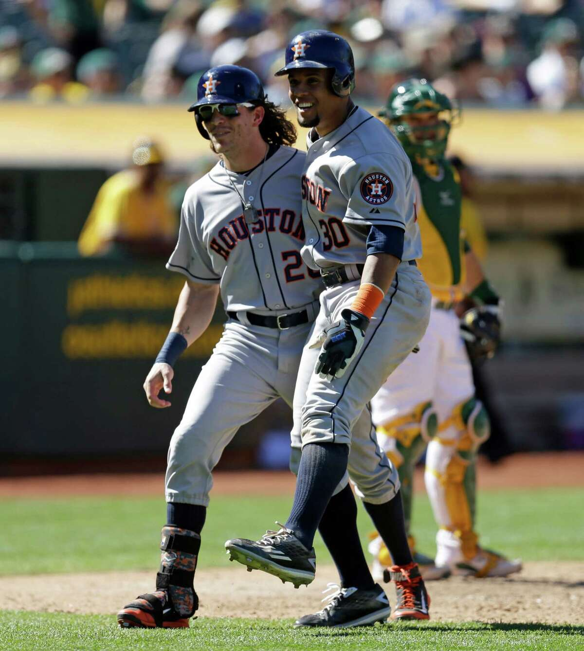 Houston Astros' Colby Rasmus, right, and Carlos Gomez (30) celebrate after Rasmus hit a three run home run off Oakland Athletics' Edward Mujica in the ninth inning of a baseball game Sunday, Aug. 9, 2015, in Oakland, Calif. (AP Photo/Ben Margot)