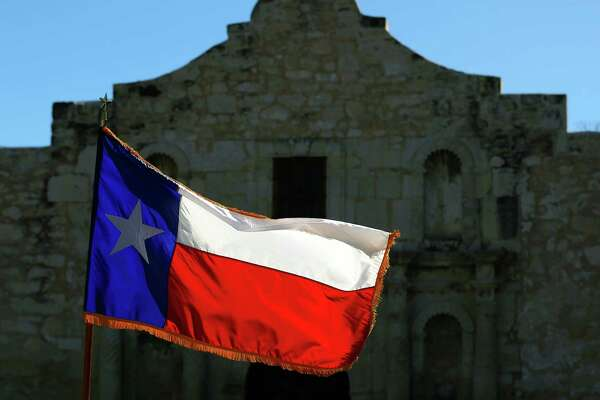 A Texas flag flies in front of the Alamo Feb. 24, 2016.