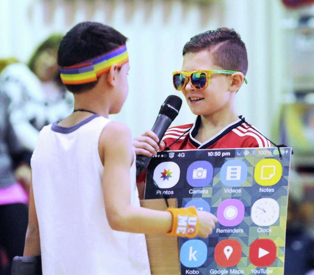 New Lebanon School third-graders Jayden Aurioles, 9, left, and Nicolas Fajardo, also 9, both dressed as digital devices, speak about what they learned recently during Friday's celebratory performance by the school's third-grade to showcase the district's digital learning program. The event was in the gymnasium at the school in the Byram section of Greenwich.