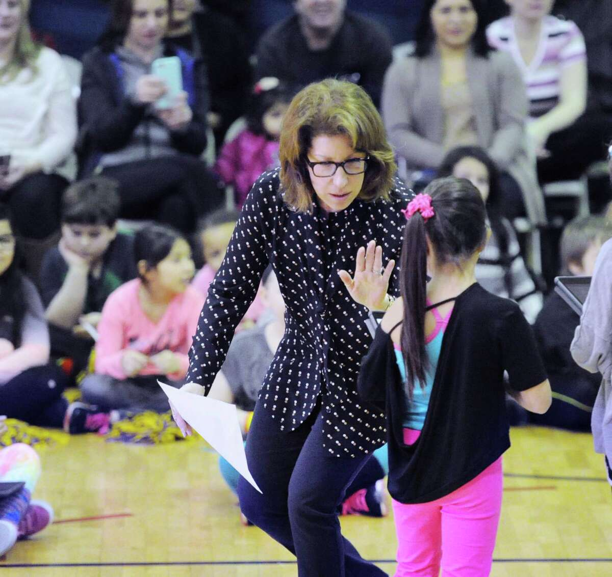 New Lebanon School music teacher Audrey Maurer received a Cyber Songstress award during the celebratory performance to showcase what third-graders have learned through the district's digital learning program in the gymnasium at the school in the Byram section of Greenwich, Conn., Friday, Feb. 26, 2016.