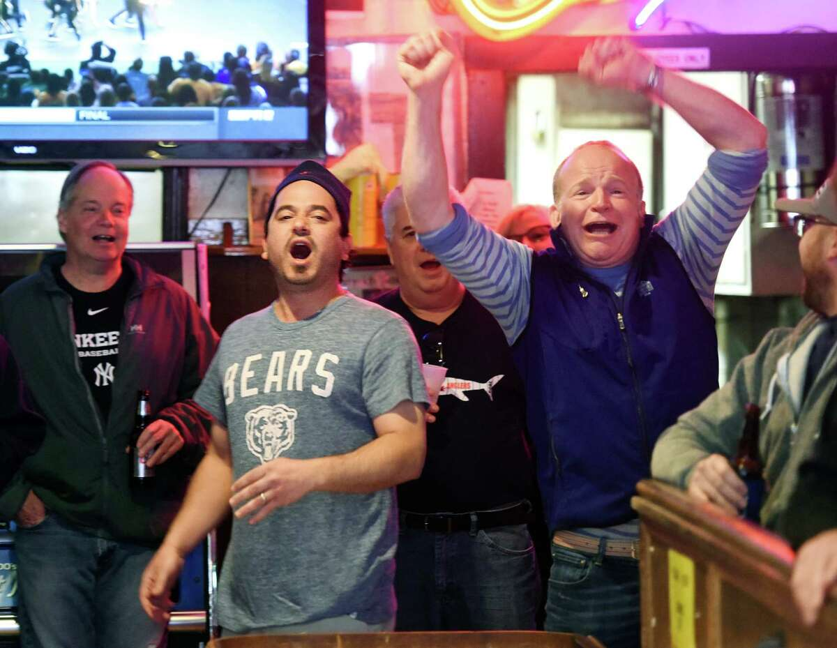 Opposing team members Dave Corbo, left, owner of Corbo's Deli, and Gib Gibson, of Old Greenwich, react to the final shot of the game during the annual shuffleboard tournament at Bruce Park Grill in Greenwich, Conn. Sunday, Feb. 28, 2016. The annual tournament, which began in 1977, draws a lot of attention as 24 teams battle it out over three weekends on the 22-foot-long shuffleboard table. First- and second-place teams get a small cash prize and a portion of proceeds from the tournament go to local groups and charities. A shuffleboard champion will be crowned as the tournament continues next Sunday, March 6.