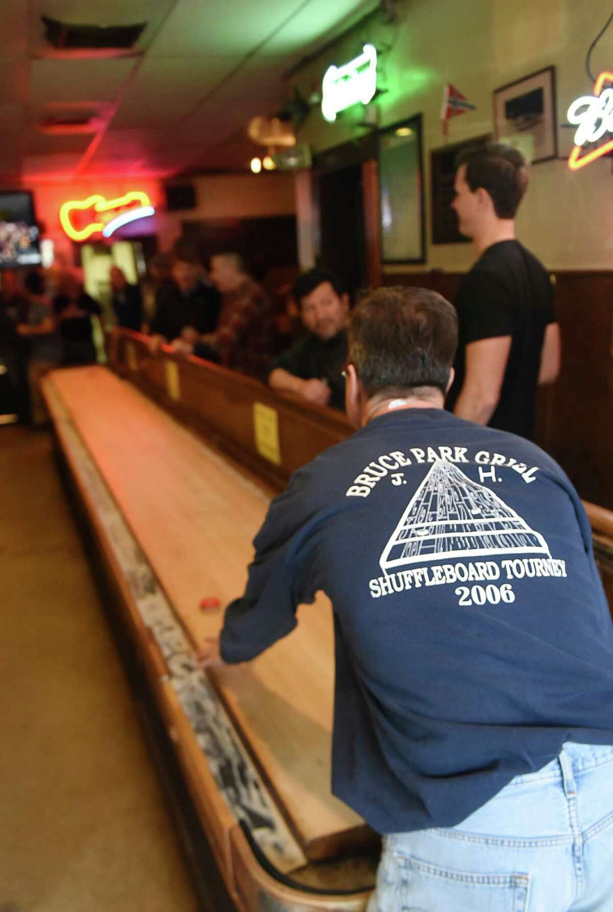 Jim Kavanagh, a lawyer from Greenwich, wears his suffleboard tournament 2006 shirt while shooting a puck during this year's annual shuffleboard tournament at Bruce Park Grill in Greenwich, Conn. Sunday, Feb. 28, 2016. The annual tournament, which began in 1977, draws a lot of attention as 24 teams battle it out over three weekends on the 22-foot-long shuffleboard table. First- and second-place teams get a small cash prize and a portion of proceeds from the tournament go to local groups and charities. A shuffleboard champion will be crowned as the tournament continues next Sunday, March 6.
