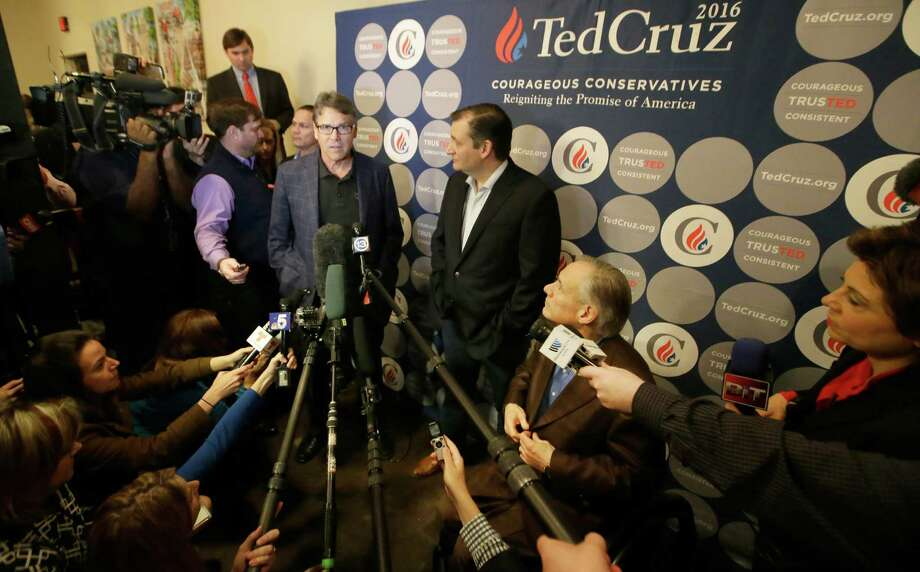 Former Texas Gov. Rick Perry, accompanied by Republican presidential candidate, Sen. Ted Cruz, R-Texas, center, and Texas Gov. Greg Abbott , seated right, speaks to reporters after a campaign rally at Gilley's nightclub, Monday, Feb. 29, 2016, in Dallas. (AP Photo/LM Otero) Photo: LM Otero, Associated Press / AP