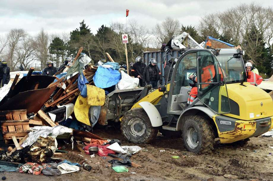 """The French authorities faced angry protesters Monday as they began to dismantle part of a vast migrant camp near the northern city of Calais after a court order last week that at least partially allowed the government to move forward with its plans to vacate the settlement, known as ?the Jungle.? Interior Minister Bernard Cazeneuve said last week that the authorities would not conduct a ?brutal evacuation? of the camp, but as workers tore down tents and dismantled ramshackle huts, clashes erupted. Some migrants lit shacks on fire to protest their evictions and threw rocks at police officers in riot gear, who pushed the migrants back with tear gas and water cannons. About 100 officers had been deployed to safeguard the site.A bulldozer dismantles shelters on February 29, 2016 in the """"Jungle"""" migrant camp in the French northern port city of Calais. Two bulldozers and around 20 workers began destroying makeshift shacks, with 30 police cars and two anti-riot vans stationed nearby.   AFP PHOTO / PHILIPPE HUGUENPHILIPPE HUGUEN/AFP/Getty Images ORG XMIT: 94 Photo: PHILIPPE HUGUEN / AFP"""