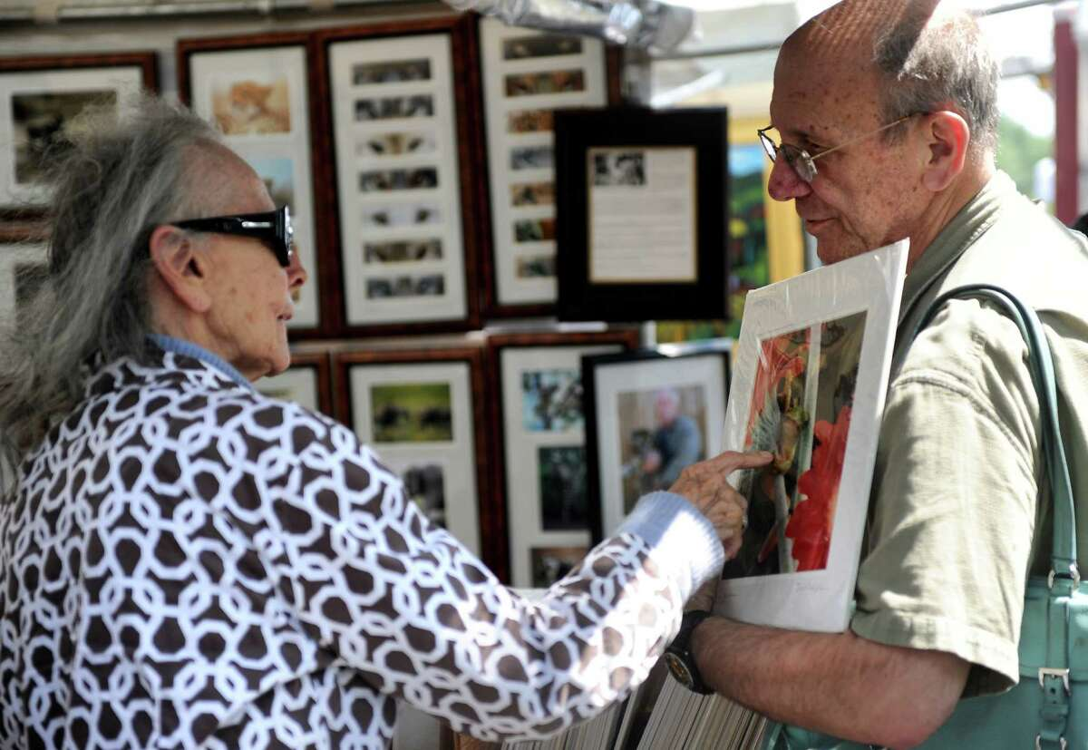 From left, Bobbie and Drew Friedman look at displays from artists along the Saugatuck River at the Westport Fine Arts Festival on Saturday, July 17, 2010.