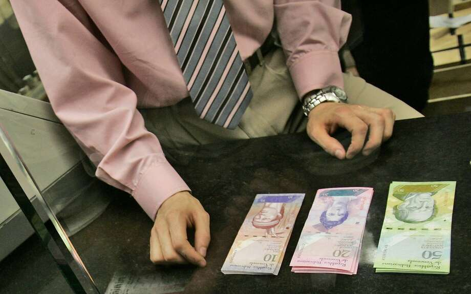 "A bank worker changes old Bolivares for the new ""Strong Bolivar."" Runaway inflation has eroded the value of the biggest bills to less than a U.S. dime. Photo: Fernando Llano, Associated Press"