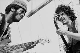 Mexican-born American musician Carlos Santana (right) and American bassist David Brown perform with the other members of Santana at Woodstock, a large rock and roll music concert, Bethel, New York, August 16, 1969..