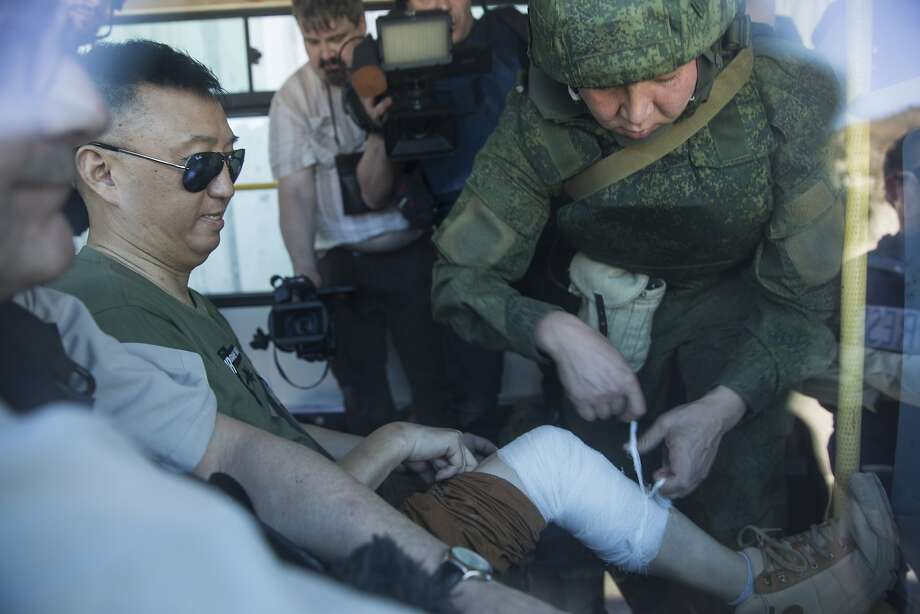 A Chinese reporter is bandaged by Russian military officer after he fell while moving to safety during explosions in Kinsibba, Syria, near the border with Turkey  Tuesday, March 1, 2016. A series of artillery shells exploded on the main street of the village of Kinsibba on Tuesday, sending a group of visiting international reporters running for cover and underscoring the limits of Syria's partial cease-fire.  (AP Photo/Pavel Golovkin) Photo: Pavel Golovkin, Associated Press