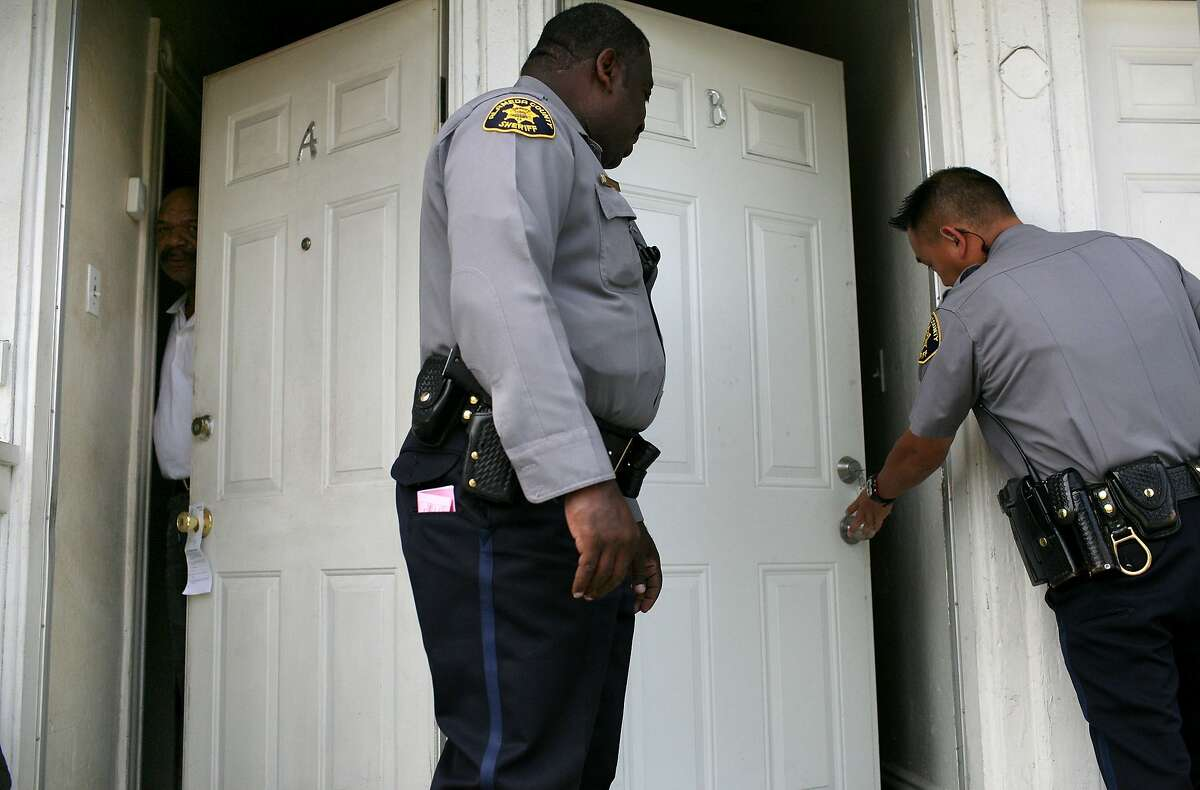 A neighbor peers out of his door as Alameda County Sheriff deputies enter an apartment to evict tenants in Oakland in 2009.