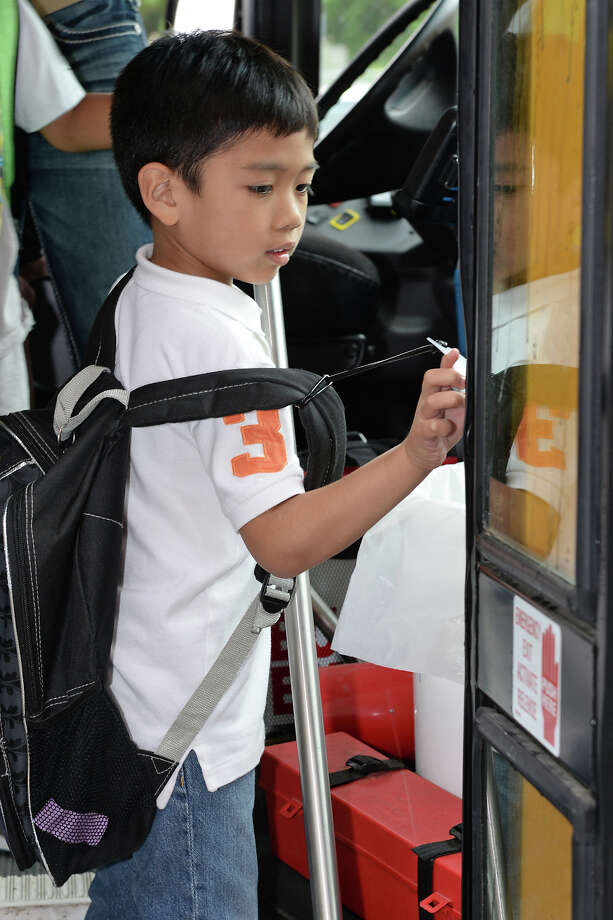 Willbern Elementary first-grader Matthew Millenas taps an ID card to a reader on his school bus, logging the time and location that he boarded the vehicle. The Cy-Fair Independent School District started phasing in the new system this school year.