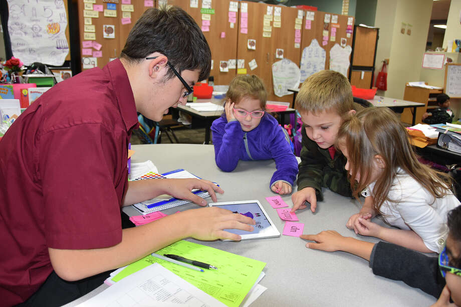 Cy-Fair High School junior Jacob Perez practices sight words with Lamkin Elementary School kindergartners Katy Kalinec, left, Brayden Crawford and Sydney Belk as part of the Instructional Practices in Education and Training class. Photo: Cy-Fair ISD
