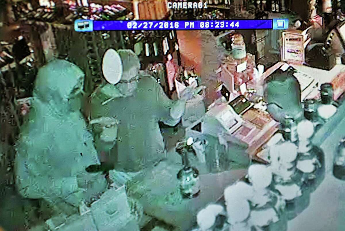An armed man, left, is caught on surveillance video robbing co owners of Bob DeMeo's Discount Wine and Liquor store Bob DeMeo and Anthony DeRusso, right, last Saturday night in Troy, NY. (John Carl D'Annibale / Times Union)