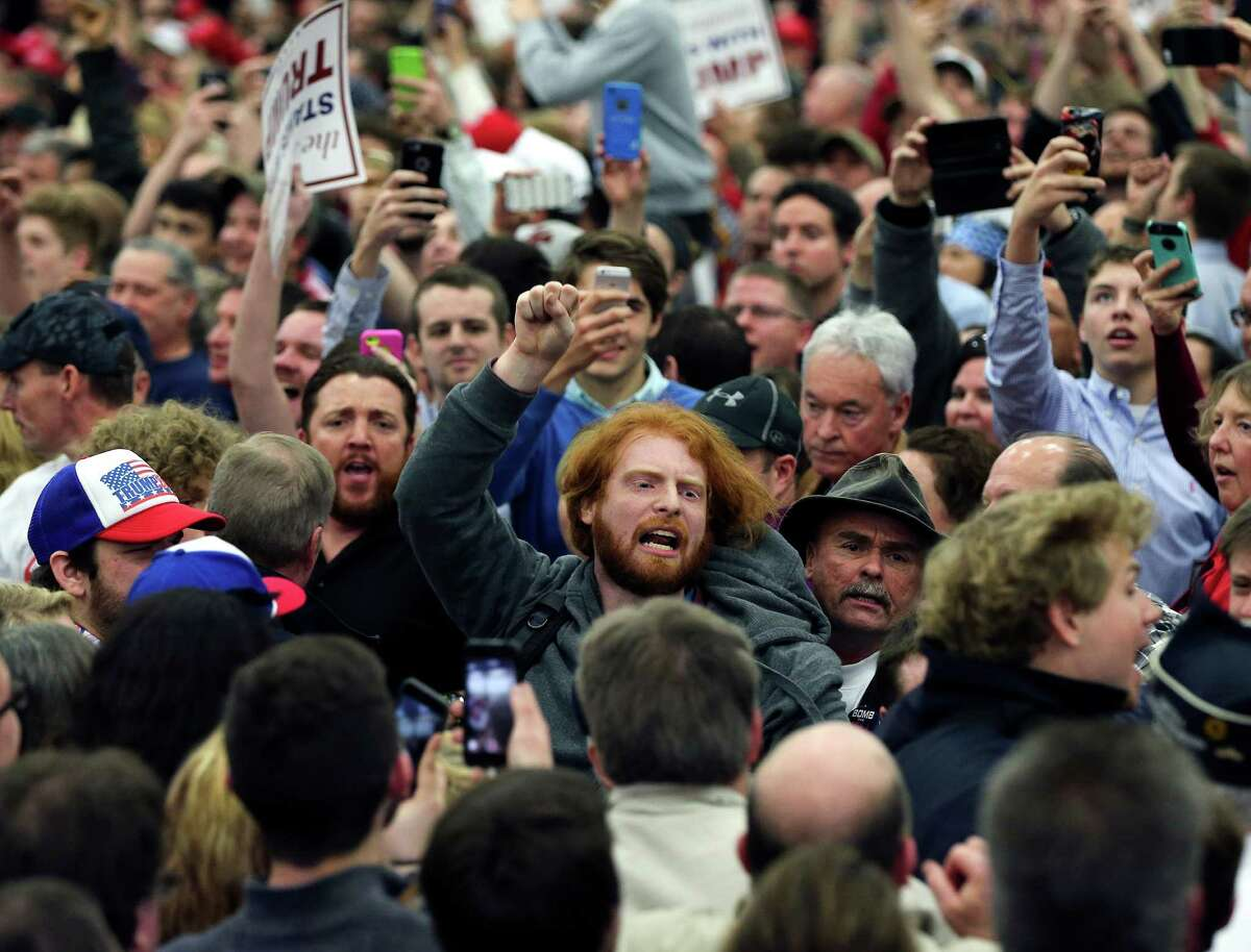 A protester is escorted out of a rally for Republican presidential candidate Donald Trump Tuesday, March 1, 2016, in Louisville, Ky.