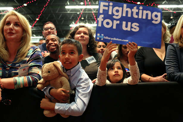 "Ilan Herrera, 8, holding his Bonham Academy class pet, ""Eduardo,"" and his sister, Alejandra Herrera, 6, listen to former President Bill Clinton speak during the Hillary for Texas Get Out The Vote Rally at the Guadalupe Cultural Arts Center Theater in San Antonio on Monday, Feb. 29, 2016."