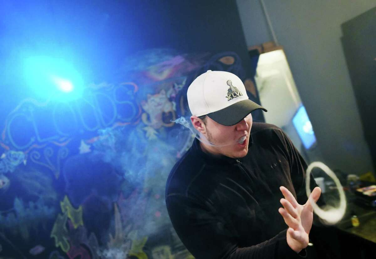 Brian Santos, of Port Chester, N.Y., blows a ring while vaping at CLOUDS Vapors & Lounge in the Byram section of Greenwich, Conn. Thursday, Feb. 18, 2016. There is propsed legislation for makers of liquid nicotine to childproof their containers, which could be just the start of an effort by Connecticut lawmakers to regulate the electronic cigarette industry and its marketing to kids.