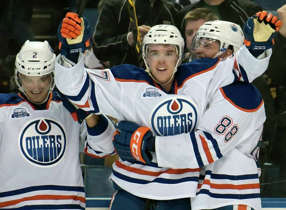 Edmonton Oilers' Andrej Sekera (2), Connor McDavid (97) and Brandon Davidson (88) celebrate after McDavid scored in overtime of an NHL hockey game against the Buffalo Sabres, Tuesday, Mar. 1, 2016, in Buffalo, N.Y.  Edmonton won 2-1. (AP Photo/Gary Wiepert) ORG XMIT: NYGW106 Photo: Gary Wiepert / FR170498 AP