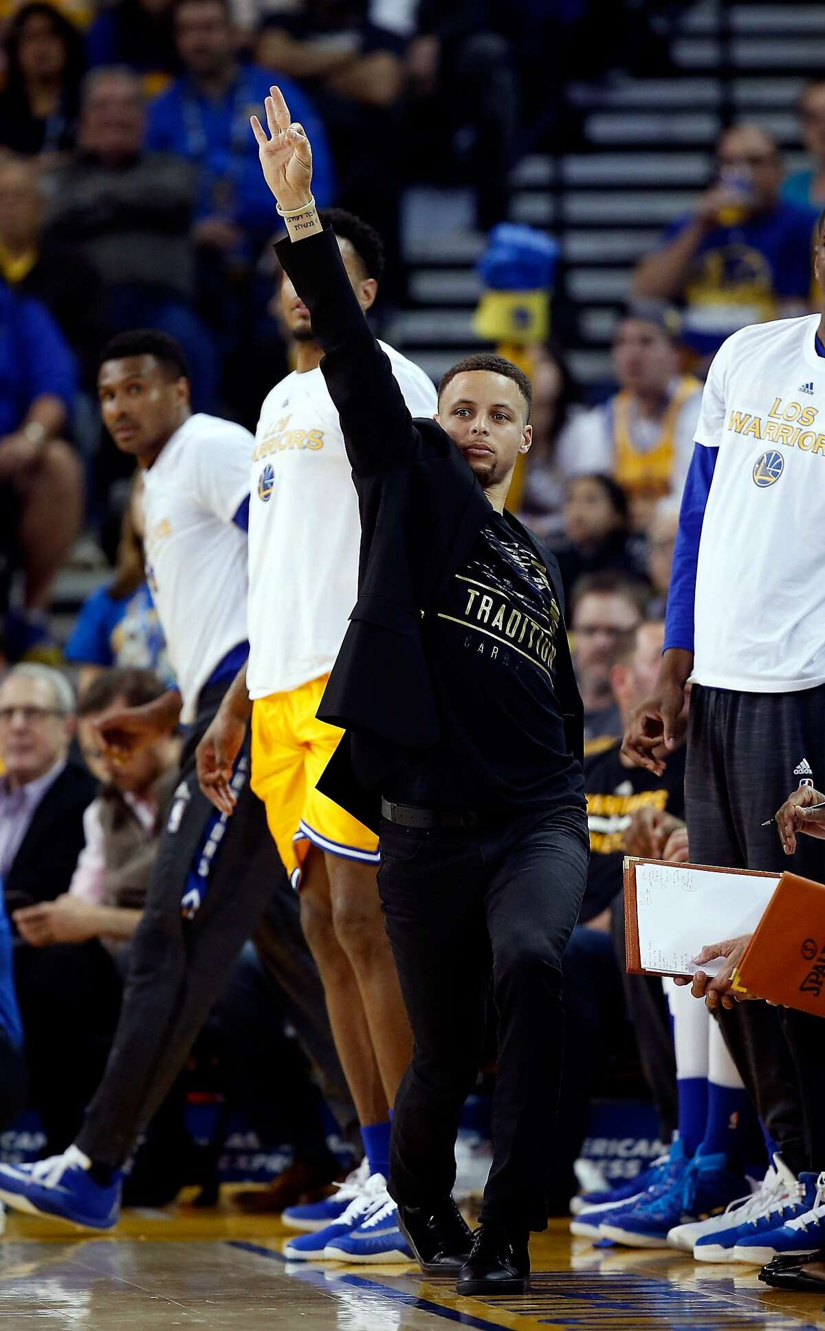 Stephen Curry, who missed the game with a sore left ankle, reacts from the sideline to a teammate's three-pointer against Atlanta on Tuesday in Oakland.
