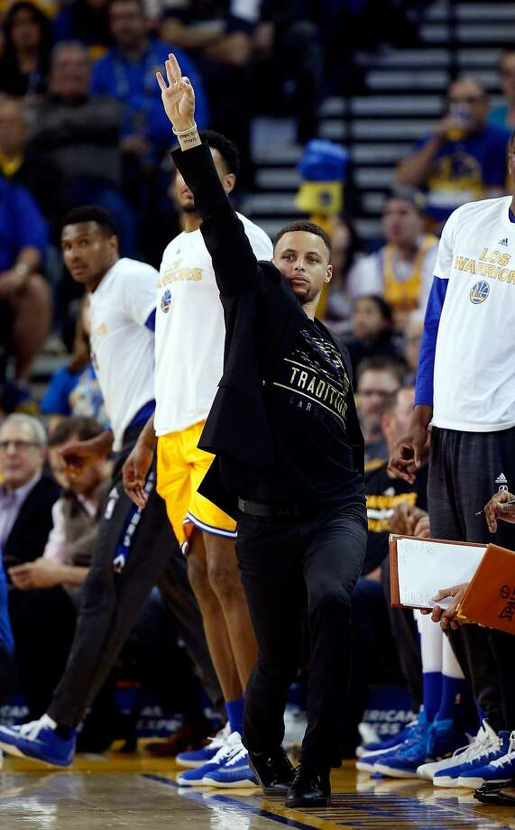 Stephen Curry, who missed the game with a sore left ankle, reacts from the sideline to a teammate's three-pointer against Atlanta on Tuesday in Oakland. Photo: Ezra Shaw, Getty Images