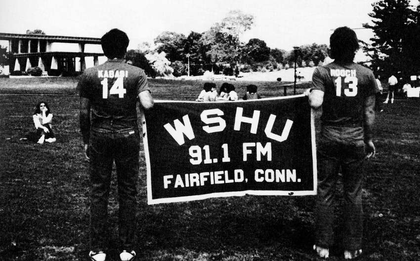 Students huold up a WSHU banner in the quad in 1984. This is the year that WSHU was accepted as a member of National Public Radio.