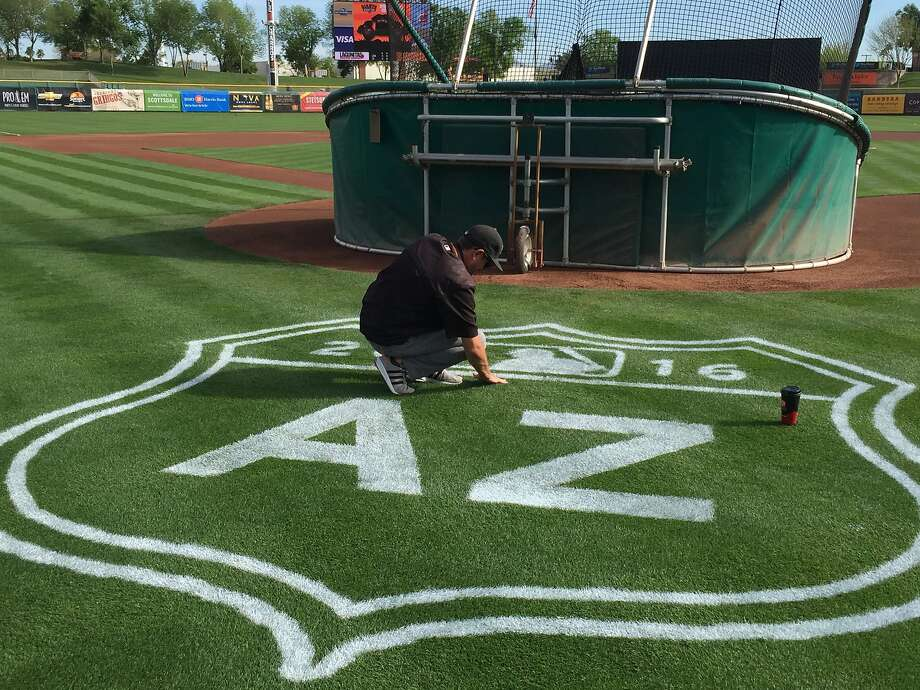 A groundskeeper touches up the new Cactus League logo hours before the Giants' opener against the Angels on Wednesday. Photo: Henry Schulman
