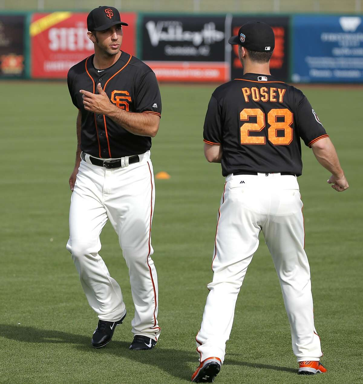 Madison Bumgarner, 40 and Buster Posey, 28 during morning workouts as the San Francisco Giants prepare to play the Los Angeles Angels at Scottsdale Stadium on Wed. March 2, 2016, in Scottsdale, Arizona.